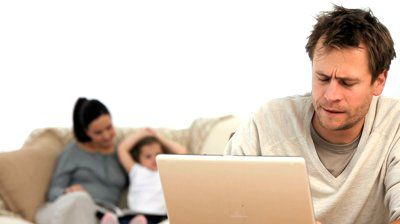 stock-footage-tired-man-on-his-laptop-while-his-family-is-on-the-sofa